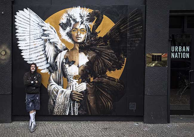 Findac with his mural outside Project M, Urban Nation