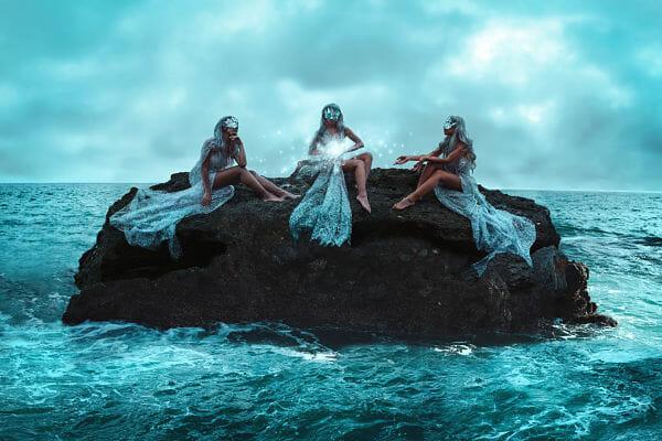 women sitting on rock in ocean