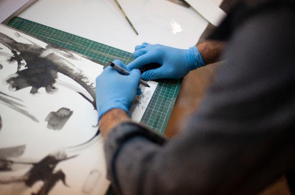 Santiago Pani signing his artwork